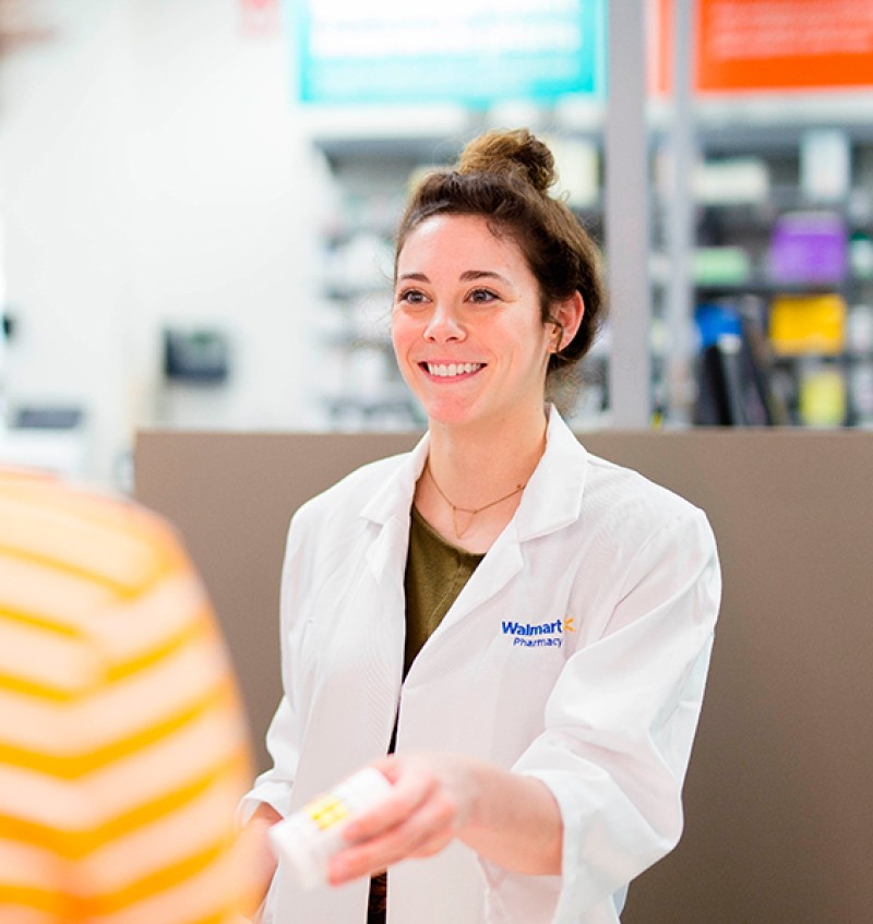 Pharmacy Technician Helping Customers At Walmart