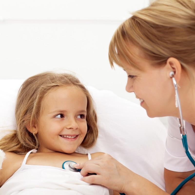 Nurse listening to a little girl's heart beat